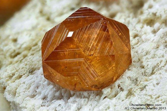 Прозрачный медово-жёлтый кристалл спессартина на породе, подходящий для огранки
