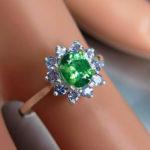 Кольцо на пальце манекена с огромным демантоидом и бриллиантами
