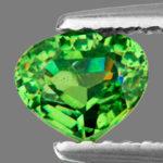 Огранённый зелёный уральский гранат в пинцете