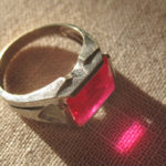 Кольцо с красным кристаллом на холсте