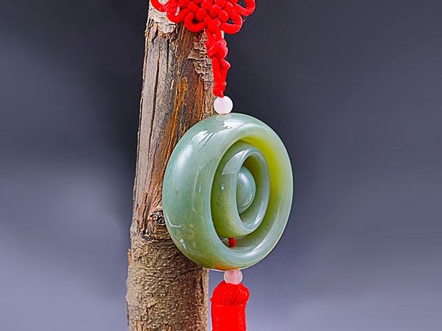 Талисман из зелёного камня на красном шнурке